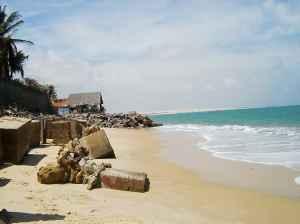 Ganze Gebäude fallen um. Im Hintergrund  notdürftige Wellenbrecher.